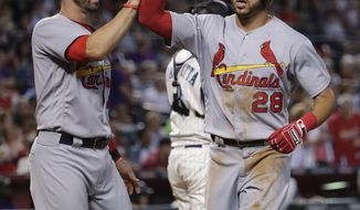St. Louis Cardinals Tommy Pham (28) high-fives Eric Fryer after Pham scored on a base hit by Randal Grichuk during the eighth inning of a baseball game against the Arizona Diamondbacks, Thursday, June 29, 2017, in Phoenix. (AP Photo/Matt York)