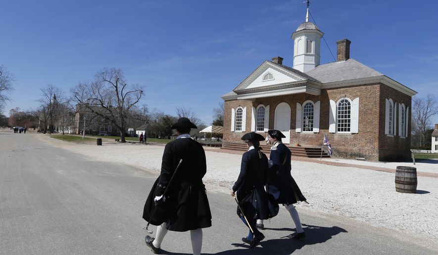 In a Wednesday March 18, 2015 file photo, Colonial interpreters walk in front of the Colonial courthouse along Duke of Gloucester street in the Colonial Williamsburg area of Williamsburg, Va. Colonial Williamsburg, facing a decline in visitors and hundreds of millions in debt, announced Thursday it will outsource many of its commercial operations in a restructuring that will include layoffs. (AP Photo/Steve Helber, File)