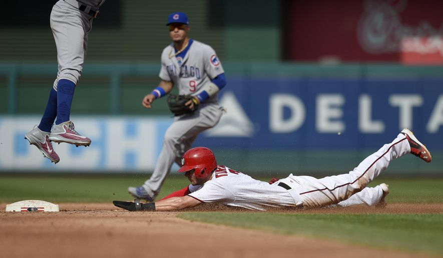 Washington Nationals' Trea Turner, bottom, steals second against Chicago Cubs shortstop Addison Russell, left, and second baseman Javier Baez, rear, during the third inning of a baseball game, Thursday, June 29, 2017, in Washington. (AP Photo/Nick Wass)