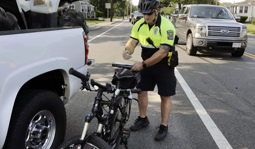 FILE- In this July 20, 2016 file photo, police officer Matthew Monteiro writes a citation for a motorist who was texting while driving, after pulling the vehicle over while patrolling on his bicycle in West Bridgewater, Mass. Drivers in Massachusetts would have to put down their phones under legislation to be taken up in the Senate on Thursday, June 29, 2017. The bill, designed to crack down on distracted driving, would prohibit cellphone use unless in hands-free mode. (AP Photo/Steven Senne, File)