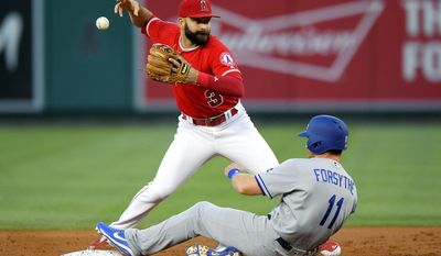 Los Angeles Dodgers' Logan Forsythe, right, is forced out at second as Los Angeles Angels second baseman Danny Espinosa loses the handle on the ball while trying to throw out Yasiel Puig at first during the second inning of a baseball game, Wednesday, June 28, 2017, in Anaheim, Calif. (AP Photo/Mark J. Terrill)