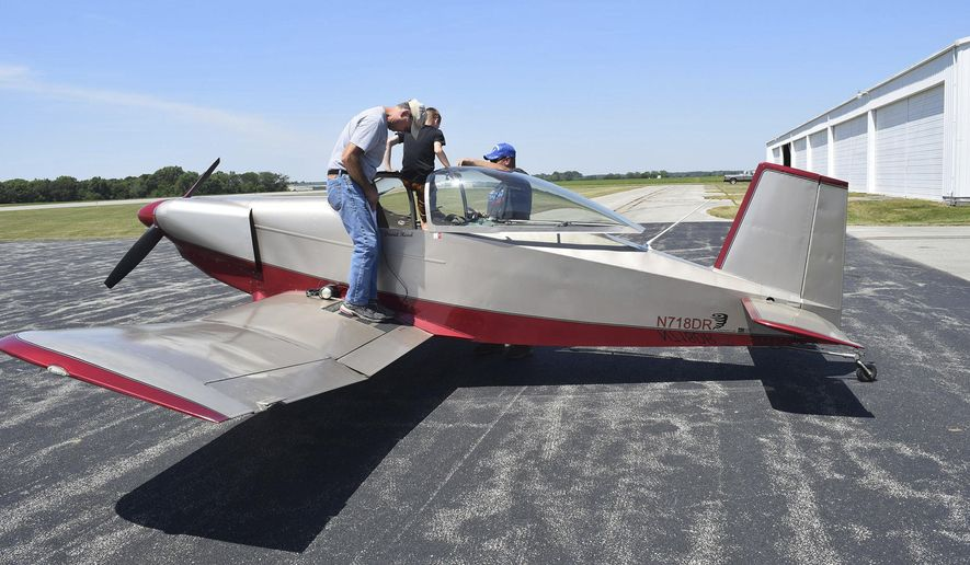 In this June 10, 2017 photo, David Read stands on the wing of his home-built Thorp T-18 as  his passenger gets help out of the aircraft at Effingham County Memorial Airport in Effingham, Ill. Read provided free flights as part of the the Experimental Aircraft Association Chapter 16 Young Eagles flight experience. Volunteer pilots, many in their own planes, provided the basic flight lessons and experience to anyone ages 8 to 17. (Dawn Schabbing/Effingham Daily News via AP)