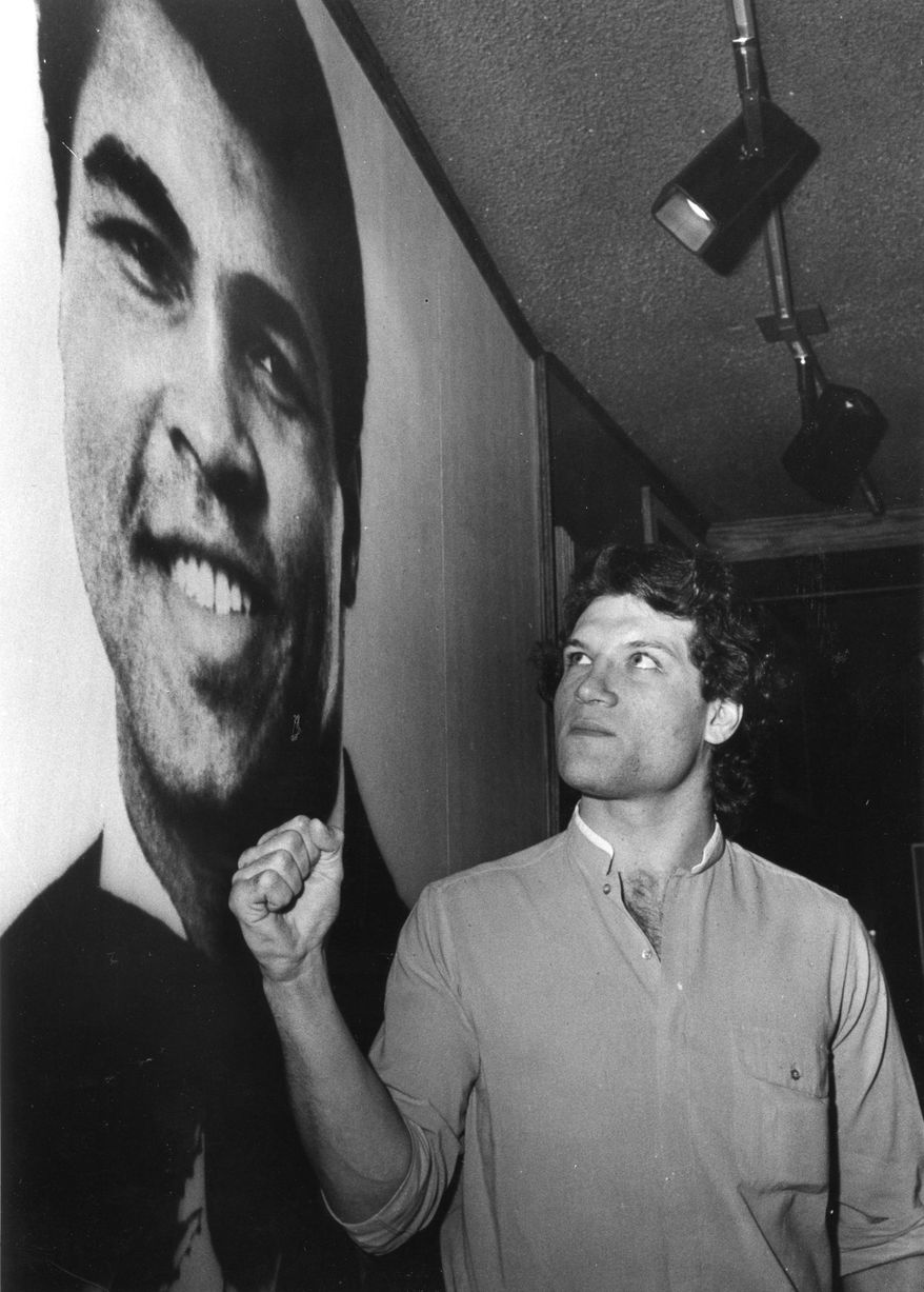 FILE - In this Feb. 24, 1983, file photo, Edmonton Oilers' Dave Semenko makes a fist in front of a poster of boxer Muhammad Ali,  in Edmonton.  Former Edmonton Oilers tough guy Dave Semenko, who protected Wayne Gretzky in the 1980s, has died. He was 59. The Oilers say Semenko died after a short battle with cancer. A team spokesman said Semenko died in Edmonton. (Charlie Palmer/The Canadian Press via AP)