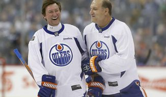 FILE - In this Oct. 21, 2016, file photo, former Edmonton Oilers hockey players Wayne Gretzky, left, and Dave Semenko joke around during a practice for the NHL's Heritage Classic Alumni game in Winnipeg, Manitoba. Former Edmonton Oilers tough guy Dave Semenko, who protected Wayne Gretzky in the 1980s, has died. He was 59. The Oilers say Semenko died after a short battle with cancer. A team spokesman said Semenko died in Edmonton. (John Woods/The Canadian Press via AP, File)