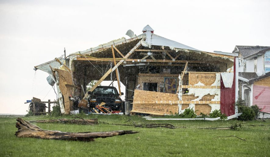 In this Wednesday, June 28, 2017 photo, a car sits in a garage, damaged after a tornado hit the property of Dee and Lynn Ossian in Farragut, Iowa. (Chris Machian/Omaha World-Herald via AP)