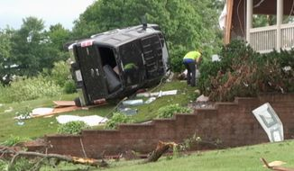 In this still frame from video provided by WQOW, a woman searches through debris with a vehicle on the lawn of a home near Martell, Wis., in Pierce County on Thursday, June 29, 2017, after a tornado touched down in western Wisconsin on Wednesday. (WQOW via AP)