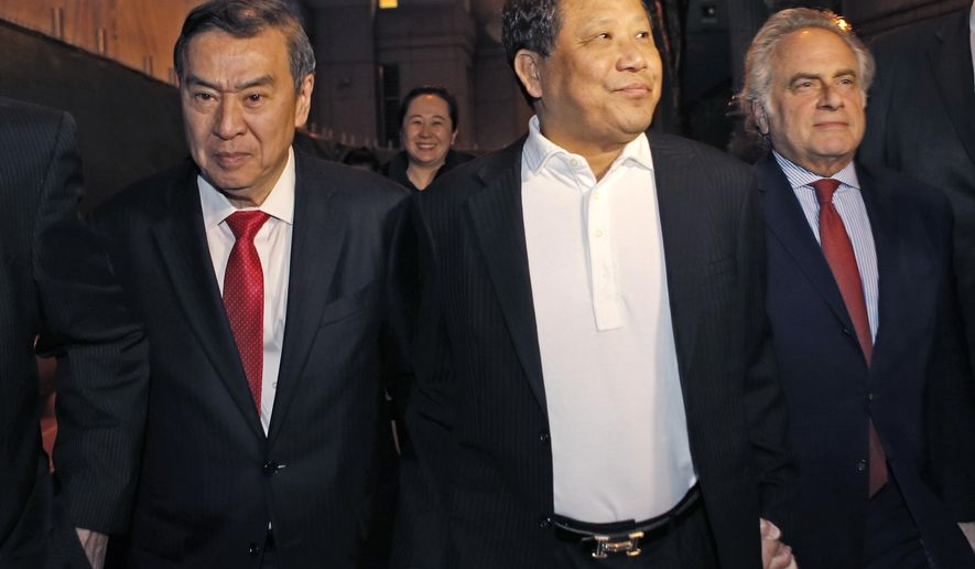 FILE - In this Oct. 26, 2015, file photo, Chinese billionaire Ng Lap Seng, center, leaves federal court with his attorney Benjamin Brafman, right, after he was released on bail in connection with a United Nations bribery scheme in New York. Prosecutor Douglas Zolkind said Thursday, June 29, 2017, during opening statements in Ng's trial that Ng corrupted two U.N. ambassadors so he could build a legacy by constructing a U.N. conference center in China. Defense attorney Tai Park countered in Manhattan federal court that Ng was a philanthropist who was betrayed by one of the ambassadors who demanded contributions from him. (AP Photo/Kathy Willens, File)