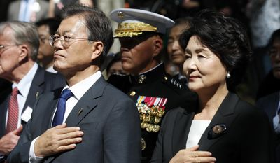 "South Korean President Moon Jae-in, left, with his wife Kim Jung-sook, and Marine Corps Commandant Gen. Robert B. Neller, center, place their hands over their hard during the playing of national anthems for South Korea and the United States during a ceremony at the ""Chosin Few Battle Monument,"" at the National Museum of the Marine Corps, Wednesday, June 28, 2017, in Triangle, Va. (AP Photo/Alex Brandon)"