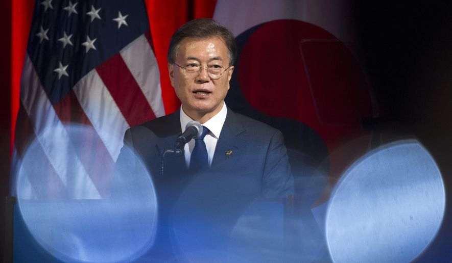 South Korean President Moon Jae-in is seen through wine glasses as he speaks to a dinner hosted by the U.S. Chamber of Commerce and the South Korean Chamber of Commerce in Washington, Wednesday, June 28, 2017. (AP Photo/Cliff Owen)