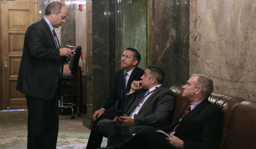 Republican Sen. Steve O'Ban, standing, talks with fellow Republican Sen. Dino Rossi, seated far left, and caucus staffers in the Senate wings before heading into a meeting to hear details on a state budget deal, Thursday, June 29, 2017, Olympia, Wash. A new two-year budget must be signed into law by midnight Friday in order to avoid a partial state government shutdown. (AP Photo/Rachel La Corte)