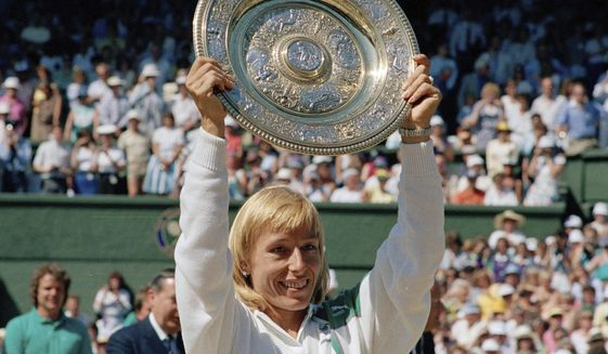In this July 4, 1987, file photo, Martina Navratilova holds up her trophy after winning the women's singles championship on the Centre Court at Wimbledon, England. (AP Photo/Robert Dear) ** FILE **