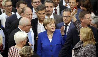 "German Chancellor Angela Merkel, center, gestures as a lawmaker raising a ""No""-polling card during a meeting of the German Federal Parliament, Bundestag, at the Reichstag building on same-sex marriage in Berlin, Germany, Friday, June 30, 2017. (AP Photo/Michael Sohn)"