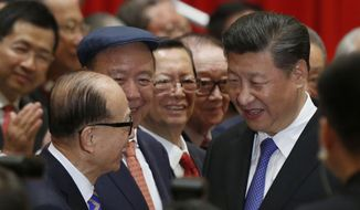 Chinese President Xi Jinping, right, is greeted by tycoon Li Ka-shing before a photo session during Xi's visit in Hong Kong, China, Friday, June 30, 2017. Xi landed in Hong Kong Thursday to mark the 20th anniversary of Beijing taking control of the former British colony. (Bobby Yip/Pool Poto via AP)