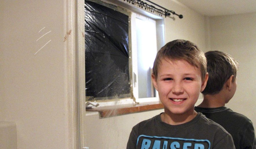 Zach Landis, 11, poses under claw marks and a blood stain left by a bear after it crashed through his bedroom window in Anchorage, Alaska, Friday, June 30, 2017. He said the bear broke through both a screen and the glass pane of a garden-level window on June 26, and left claw marks and blood on the wall as it scrambled to get back outside. No one was hurt, just shaken up. (AP Photo/Mark Thiessen)