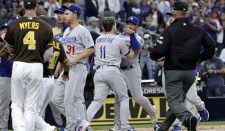 Los Angeles Dodgers manager Dave Roberts, center rear, is held back by third baseman Logan Forsythe (11) as the Dodgers and the San Diego Padres come onto the field during an argument in the second inning of a baseball game Friday, June 30, 2017, in San Diego. (AP Photo/Gregory Bull)