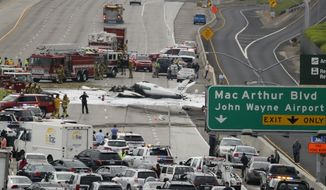 Emergency responders gather round the crash of a Cessna 310 aircraft on Interstate 405, just short of a runway at John Wayne Airport in Costa Mesa, Calif., Friday, June 30, 2017. Two people were injured in the small plane crash. (AP Photo/Chris Carlson)