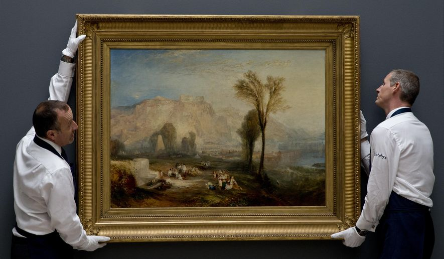 Members of staff at Sotheby's auction house adjust an oil painting entitled ' Ehrenbreitstein' (1835), by British artist J.M.W.Turner, in London, Friday, June 30, 2017. The painting is expected to be sold for some 15-25 million pounds, (US$18.7-31.2 million, euro 17.3-28.9 million) when sold at auction on July 5. (AP Photo/Alastair Grant)