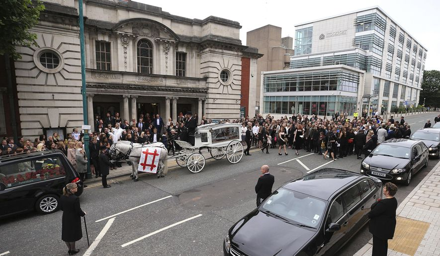 "The coffin of Martyn Hett, who was killed in the Manchester Arena bombing, leaves Stockport Town Hall Plaza following his funeral service, in Stockport, England, Friday June 30, 2017. Mariah Carey sent a video message and stars of the British TV show ""Coronation Street"" were among the mourners at a funeral for Manchester concert bombing victim Martyn Hett. Hett was one of 22 people killed when a suicide bomber struck concertgoers leaving an Ariana Grande show in the northwest England city on May 22.  (Peter Byrne/PA via AP)"