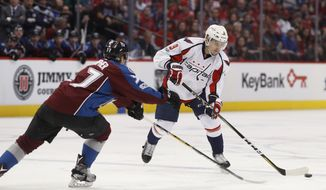 FILE - In this March 29, 2017 file photo Washington Capitals defenseman Dmitry Orlov, right, of Russia, passes the puck as Colorado Avalanche left wing J.T. Compher defends in the second period of an NHL hockey game in Denver. The Washington Capitals have re-signed Orlov to a $30.6 million, six-year deal. (AP Photo/David Zalubowski, File)