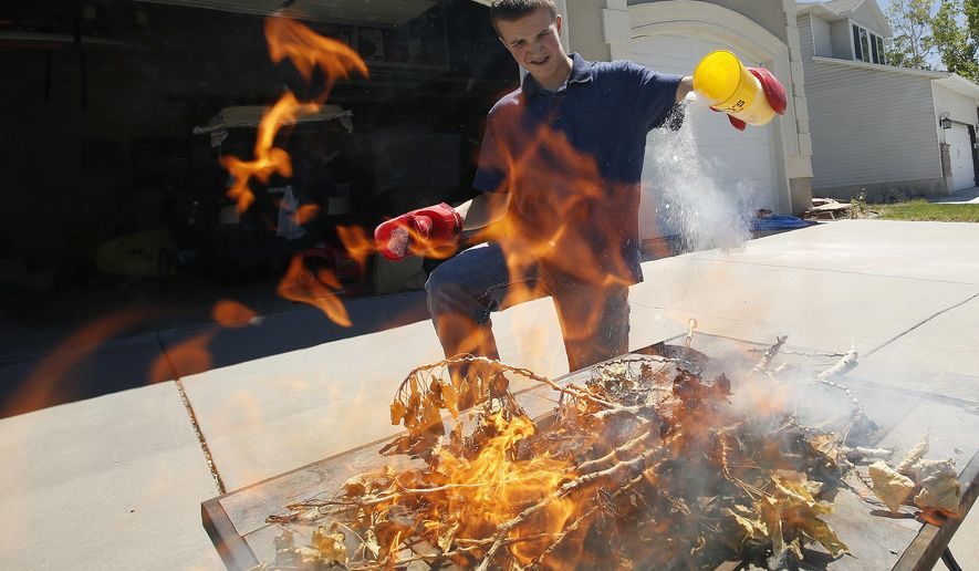 In this Friday, June 23, 2017 photo, Gavin Norman, 13, uses a technique he invented to put out a fire with dry ice at his home in Stansbury Park, Utah. Norman was a state level winner in a national science contest. (Jeffrey D. Allred/The Deseret News via AP)