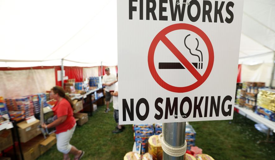 In this Thursday, June 15, 2017 photo, a no smoking sign is seen in an Iowa Fireworks Company tent, in Adel, Iowa. Decades after a devastating fire caused by a dropped sparkler led Iowa to ban fireworks, the explosives are now legal in the state. But fireworks retailers and people eager to set off the explosives are finding that many local officials remain keenly aware of that fire so many years ago. (AP Photo/Charlie Neibergall)
