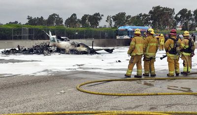 This photo provided by the Orange County Fire Authority shows firefighters standing by the wreckage of a twin-engine prop jet after it crashed on Interstate 405, just short of the runway at John Wayne Orange County Airport, in Costa Mesa, Calif., Friday, June 30, 2017. Officials said two people were injured and were taken by helicopter to a hospital. The freeway was shut down in both directions. (Orange County Fire Authority via AP)