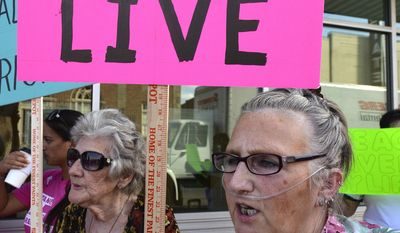 Tonya Robinson, of Elizabethtown, Ky., a lung cancer survivor, protests the arrival of Senate Majority Leader Mitch McConnell, R-Ky., at the Lincoln Day Dinner, Friday, June 30, 2017, in Elizabethtown, Ky. (AP Photo/Timothy D. Easley)