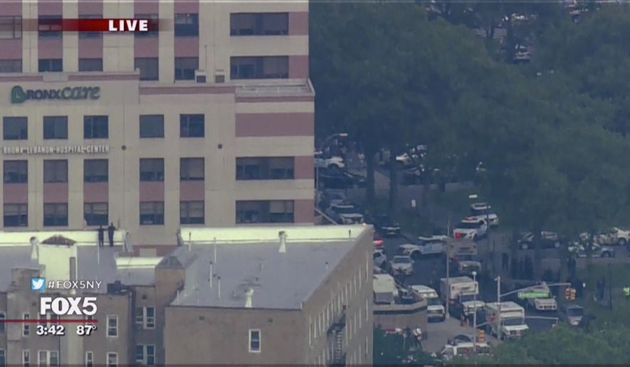 In this image taken from video provided by WNYW, police and other emergency personnel respond to Bronx Lebanon Hospital in New York after a gunman opened fire there on Friday, June 30, 2017. (WNYW via AP)