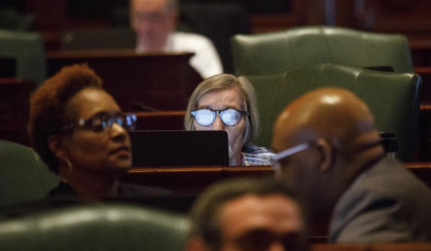 """FILE - In this June 28, 2017, file photo, Rep. Barbara Flynn Currie, D-Chicago, center, works on a laptop at her desk on the House floor at the Capitol in Springfield, Ill. Illinois is hours away from entering its third fiscal year without a state budget, territory that could mean some universities won't be able to offer federal financial aid, road construction and Powerball ticket sales will halt and the state's credit rating will be downgraded to """"junk."""" (Rich Saal/The State Journal-Register via AP File)"""