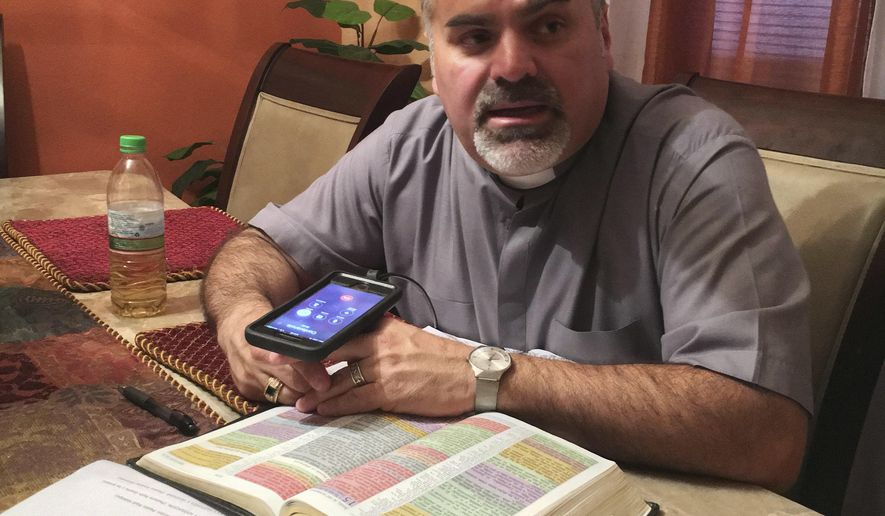 In this Friday, June 23, 2017 photo, Pastor Julio Barquero, a lay minister in the Disciples of Christ, holds a conference call bible study and prayer session with attendees to afraid to go to church in Houston. Many of the callers are undocumented immigrants. (AP Photo/ John L. Mone)
