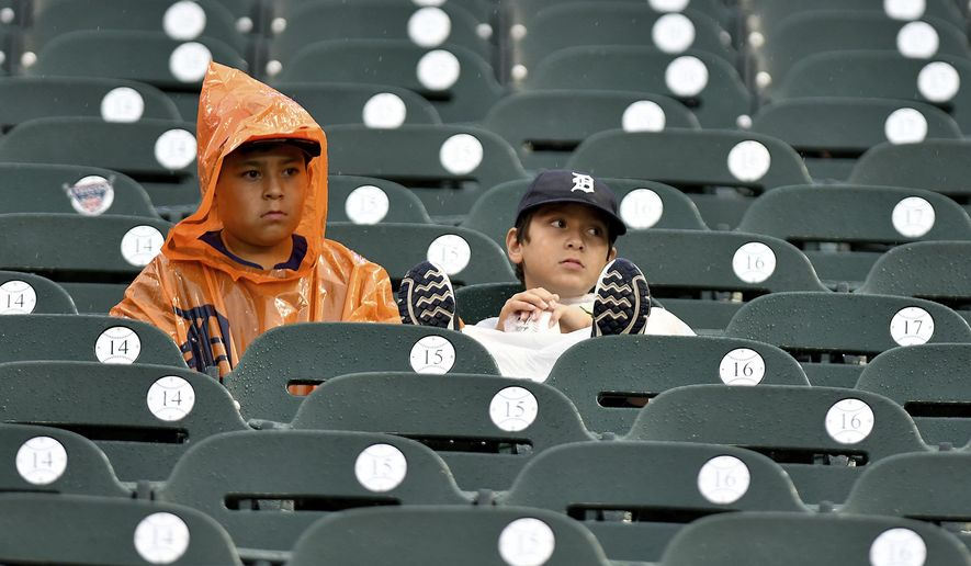 Jacob Salamon, 11, left, and his brother Jeremiah, 8, sit in their seats in a steady rain after it was announced that a baseball game between the Detroit Tigers and the Cleveland Indians was postponed, Friday, June 30, 2017 in Detroit. The brothers had traveled from Austin, Texas, with their family to watch the Tigers. (AP Photo/Lon Horwedel)
