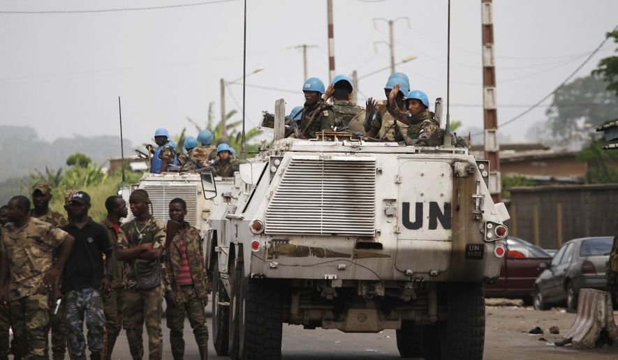 FILE - In this Saturday, April 9, 2011, file photo, United Nations soldiers wave as they drive past forces loyal to Alassane Ouattara, at a republican forces operating base on the outskirts of Abidjan, Ivory Coast. The U.N. peacekeeping mission in Ivory Coast is coming to an end Friday, June 30, 2017, 13 years after forces intervened to implement a peace agreement that left the war-wracked economic giant split into two pieces. (AP Photo/Rebecca Blackwell, File)