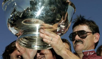 FILE - In this Aug. 5, 2006, file photo, driver John Campbell, right, holds up the Hambletonian trophy at Meadowlands Racetrack in East Rutherford, N.J., after winning the prestigious race for the sixth time. Campbell bids farewell to the Meadowlands, making his final drives at the track that helped the Hall of Famer become harness racing's career leader in purses. The 62-year-old Campbell is scheduled to drive in five races at the Meadowlands Racetrack on Friday night, June 30, 2017. (AP Photo/Mel Evans, File)