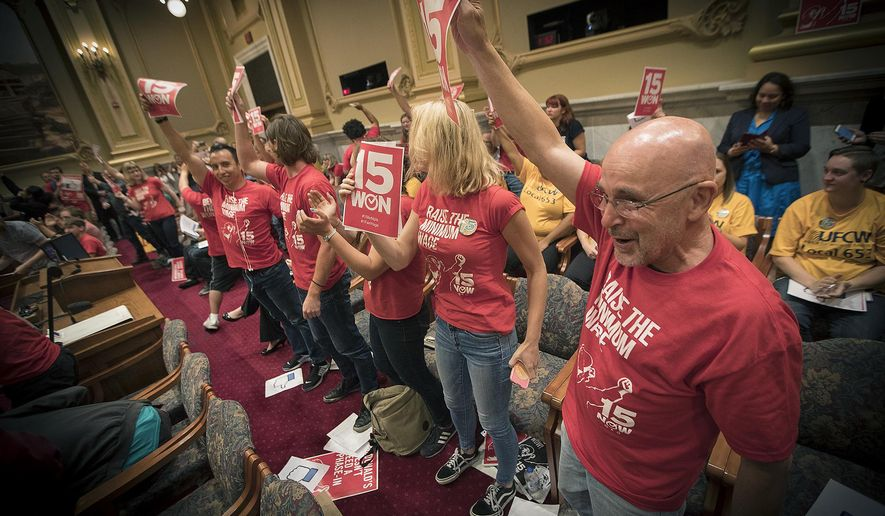 Supporters of the $15 minimum wage increase celebrated after it was passed by the City Council at City Hall, Friday, June 30, 2017 in Minneapolis. Minneapolis became the latest city to approve a big hike in its minimum wage, with the City Council voting to hike it to $15 by 2022 (Elizabeth Flores/Star Tribune via AP)