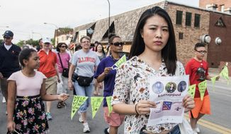 Fangqin Wan, a graduate student at the University of Illinois, walks for Yingying Zhang, a Chinese scholar who went missing three weeks ago, Thursday, June 29, 2017, in Urbana, Ill. Illinois students and others from the wider community are gathering at the Urbana-Champaign campus to show support for the Chinese scholar who disappeared three weeks ago. (Holly Hart/The News-Gazette via AP)