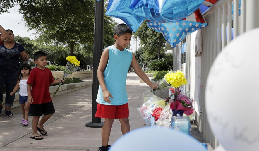 Tony Alameda, right, places flowers at a make-shift memorial at the San Antonio Police headquarters, Friday, June 30, 2017, in San Antonio. Two San Antonio police officers were wounded critically and a suspect was killed in a shootout on a street just north of the city's downtown section. (AP Photo/Eric Gay)