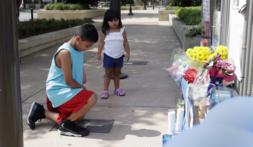 Tony Alameda, left, prays after placing flowers at a make-shift memorial at the San Antonio Police headquarters, Friday, June 30, 2017, in San Antonio. Two San Antonio police officers were wounded critically and a suspect was killed in a shootout on a street just north of the city's downtown section. (AP Photo/Eric Gay)