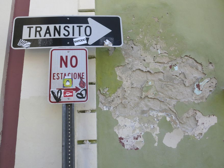 In this June 22, 2017 photo, a no parking and one way sign stand next to the deteriorating wall of an abandoned building in the historic area of Puerto Rico's capital in San Juan, Puerto Rico. Nearly 40 key buildings in San Juan's metropolitan area are in danger of being lost, according to Andy Rivera, an architect who founded the Puerto Rico Historic Building Drawing Society. (AP Photo/Danica Coto)