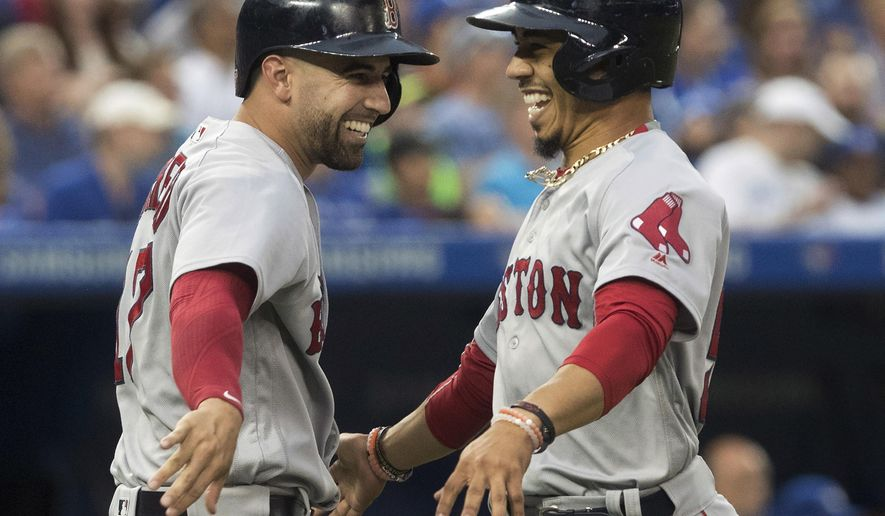 Boston Red Sox's Mookie Betts, right, celebrates with teammate Deven Marrero after scoring on a Dustin Pedroia double during the fifth inning against the Toronto Blue Jays in a baseball game in Toronto on Friday, June 30, 2017. (Fred Thornhill/The Canadian Press via AP)