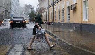 A woman crosses a flooded street in heavy rain during a thunderstorm in Moscow, Russia, Friday, June 30, 2017. A massive thunderstorm in the Moscow region has killed at least one and injured several people. (AP Photo/Denis Tyrin)