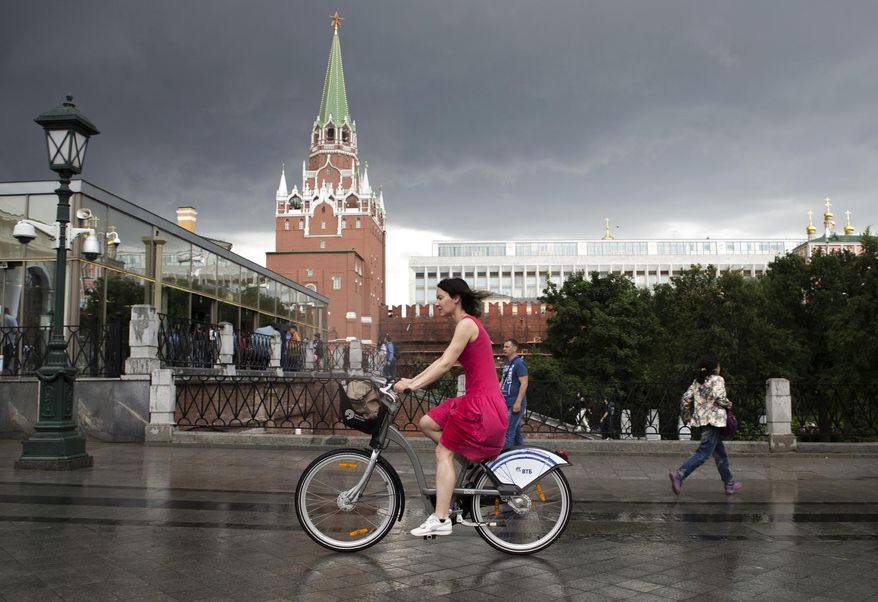 A woman rides bicycle past the Kremlin before a thunderstorm in Moscow, Russia, Friday, June 30, 2017. A massive thunderstorm in the Moscow region has killed at least one and injured several people. (AP Photo/Denis Tyrin)