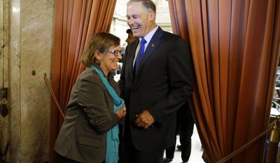 Washington Gov. Jay Inslee right, greets Rep. June Robinson, D-Everett, left, in the wings of the House chamber at the Capitol, after the Washington Legislature approved a new two-year state operating budget, sending the spending plan to Inslee in time to avert a partial government shutdown Friday, June 30, 2017, in Olympia, Wash. (AP Photo/Ted S. Warren)