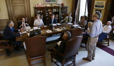 Washington Gov. Jay Inslee, left, meets with staff members in his office as they review the state operating budget passed by the Legislature earlier in the day, Friday, June 30, 2017, at the Capitol in Olympia, Wash. (AP Photo/Ted S. Warren)