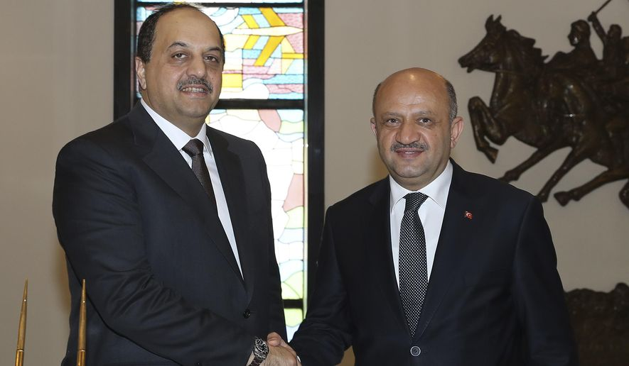 Turkey's Defence Minister Fikri Isik, right, shakes hands with Qatar's counterpart Khalid bin Mohammed al-Attiyah, prior to their meeting in Ankara, Turkey, Friday, June 30, 2017. The ministers held talks as the Gulf nation's feud with four other major Arab states deepens amid a sweeping list of demands to Doha, including the closure of a Turkish military base there. (Defence Ministry via AP, Pool)