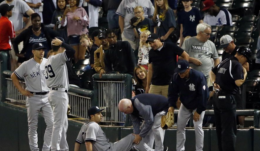New York Yankees' Dustin Fowler is checked by a team trainer after an injury during the first inning of the team's baseball game against the Chicago White Sox on Thursday, June 29, 2017, in Chicago. (AP Photo/Nam Y. Huh)