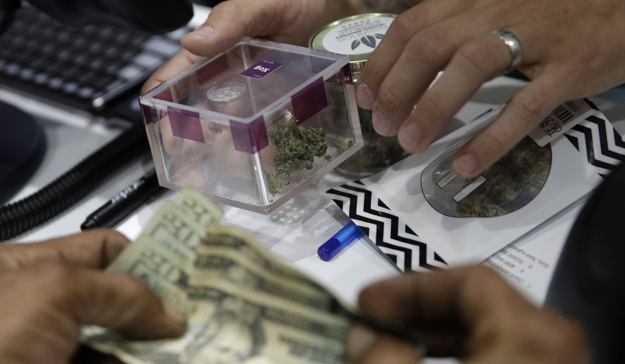 A person buys marijuana at the Essence cannabis dispensary, Saturday, July 1, 2017, in Las Vegas. Nevada dispensaries were legally allowed to sell recreational marijuana starting at 12:01 a.m. Saturday. (AP Photo/John Locher)
