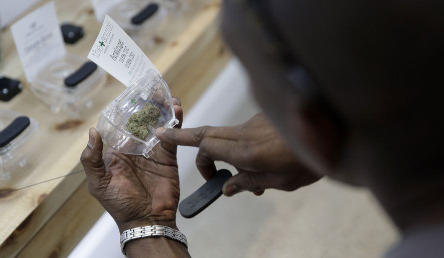 A man examines marijuana for sale at The Source dispensary, Saturday, July 1, 2017, in Las Vegas. (AP Photo/John Locher)