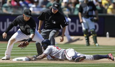 Atlanta Braves' Danny Santana, right, slides into steal third base ahead of the tag by Oakland Athletics' Ryon Healy in the seventh inning of a baseball game Saturday, July 1, 2017, in Oakland, Calif. (AP Photo/Ben Margot)