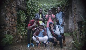 In this photo taken Tuesday June 27, 2017, Lionel Fotot, wearing a brown leather jacket and white pants, poses for a photograph with other members of the One Force Hip Hop band in Bangui, Central African Republic. Fotot once watched a crowd kill a 6-year-old Muslim boy with a machete. He can't shake the memories of the brutalities he witnessed as Central African Republic collapsed into sectarian violence. So the young hip hop artist was heartened when his One Force group, comprised of Christians and Muslims, performed to a packed crowd at the largest venue in the capital, the 20,000-seat Barthelemy Boganda Stadium. (AP Photo/Zack Baddorf)