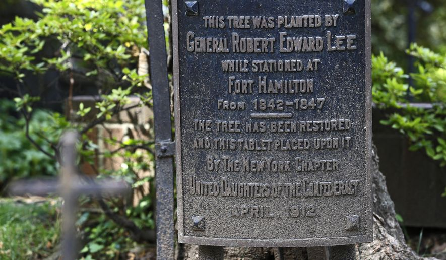 In this June 27, 2017 photo, a plaque marks a maple tree planted by Confederate Gen. Robert E. Lee on the grounds of St. John's Episcopal Church in the Brooklyn borough of New York. The plaque marking the tree was installed in 1912 by the New York chapter of the United Daughters of the Confederacy. General Lee was stationed at the nearby U.S. Army base at Fort Hamilton from 1842-1847 and reportedly worshipped at the church as did other army generals based there. The tree has been restored, but the church is up for sale. U.S. Rep. Yvette Clark, (D, Brooklyn), questions the existence of two memorials to General Robert E. Lee within the nearby U.S. Army base where the base's main boulevard is named after him. Clarke claims the South has turned a page on this chapter in history and says it's time for Brooklyn to do the same. (AP Photo/Kathy Willens)